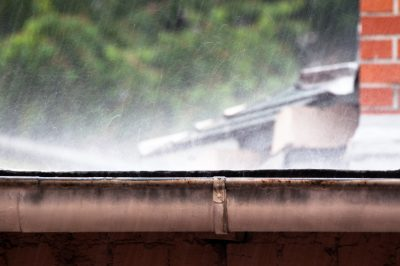 rain falling heavily on roof in summer